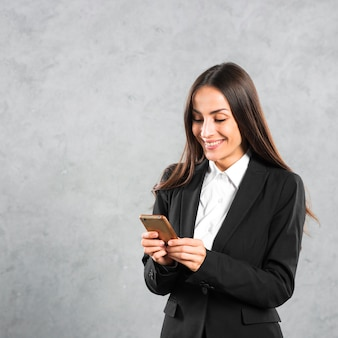 Souriante jeune femme d'affaires à l'aide de téléphone intelligent permanent sur fond de béton gris