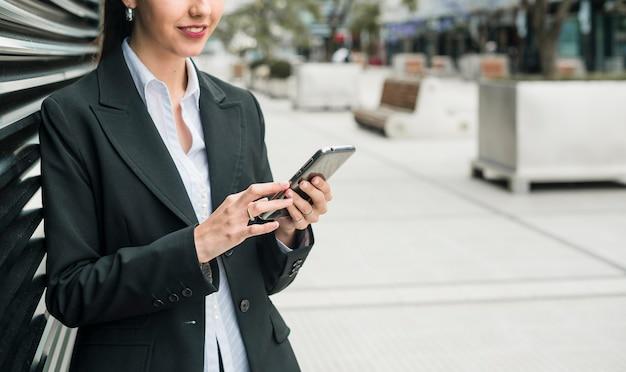 Souriante jeune femme d'affaires à l'aide de téléphone intelligent