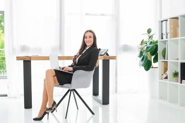 Souriante jeune femme d'affaires assis sur le lieu de travail avec un ordinateur portable sur ses genoux