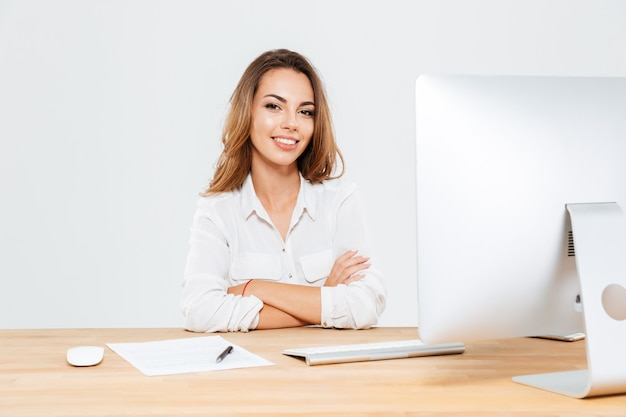 Souriante jeune femme d'affaires assise au bureau avec un ordinateur portable avec les mains jointes