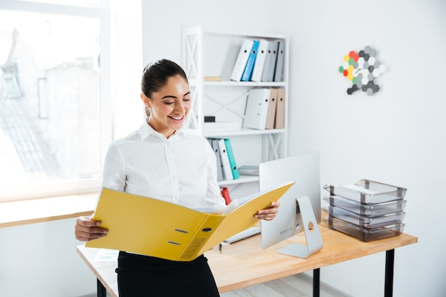Souriante jeune femme d'affaires assise sur la table avec des documents au bureau