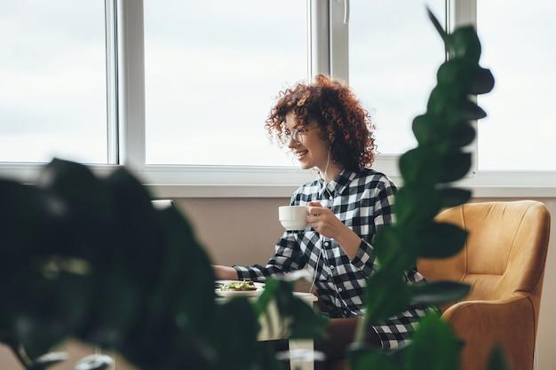 Souriante jeune femme d'affaires aux cheveux bouclés et lunettes boit une tasse de thé tout en mangeant quelque chose à l'ordinateur portable