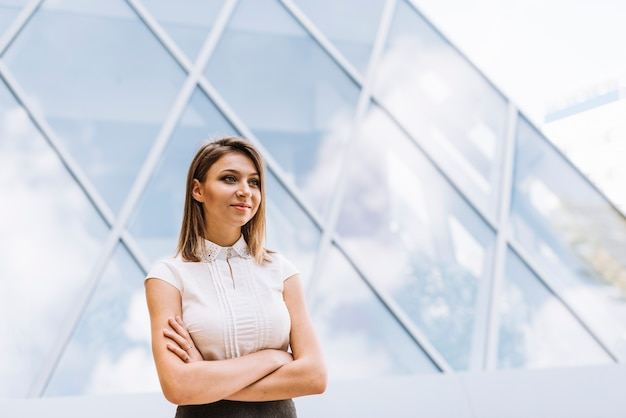 Souriante jeune femme d'affaires debout devant un bâtiment moderne