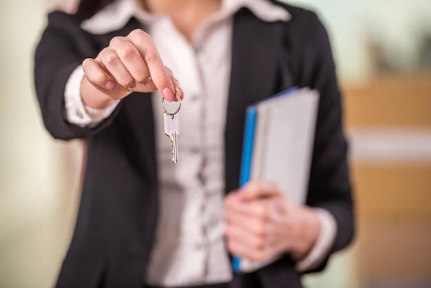 Souriante jeune femme d'affaires détenant la clé. focus sur la clé.