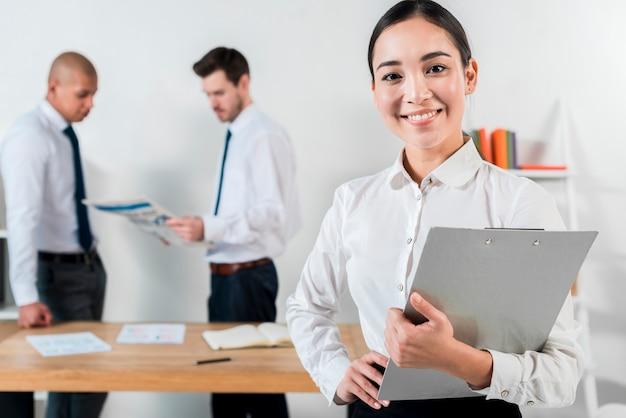 Souriante jeune femme d'affaires détenant le presse-papiers à la main avec deux homme d'affaires travaillant à l'arrière-plan