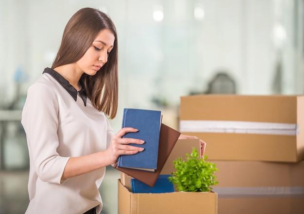 Souriante jeune femme d'affaires, emballage de boîtes au bureau.