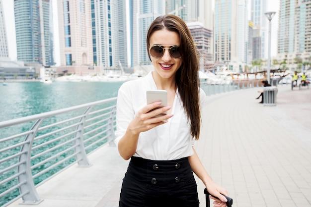 Souriante jeune femme d'affaires marchant dans la ville avec téléphone et bagages.