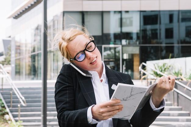 Souriante jeune femme d'affaires, parler au téléphone cellulaire tenant le journal dans la main