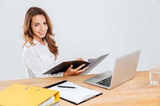 Souriante jeune femme d'affaires se réveillant avec des documents et un ordinateur portable sur fond blanc