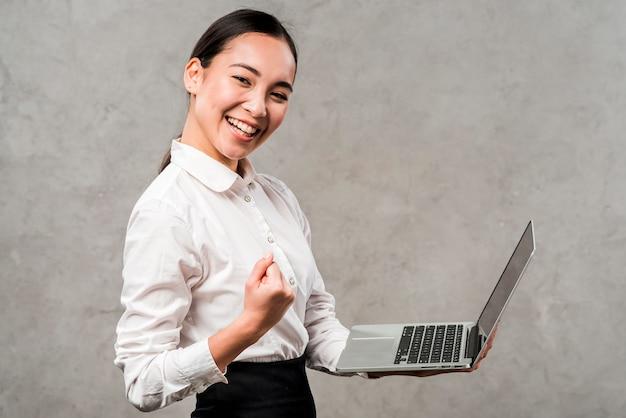 Souriante jeune femme d'affaires tenant un ordinateur portable dans la main, serrant son poing contre le mur gris