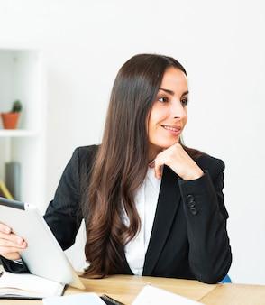 Souriante jeune femme d'affaires tenant une tablette numérique dans la main à la recherche de suite