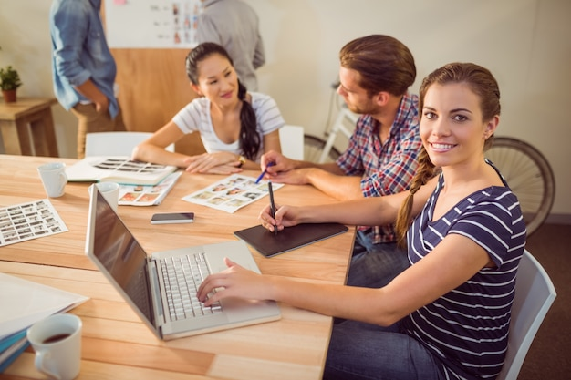 Souriante jeune femme d'affaires utilisant un ordinateur portable