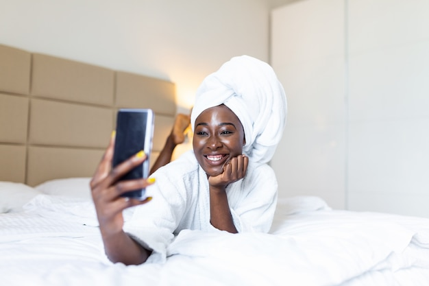 Souriante jeune femme africaine allongée sur le lit en peignoir avec son téléphone portable prenant un selfie.