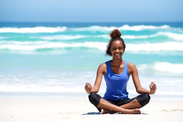 Souriante jeune femme africaine dans la pose d'yoga