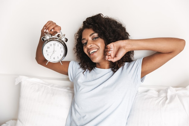 Souriante jeune femme africaine montrant réveil
