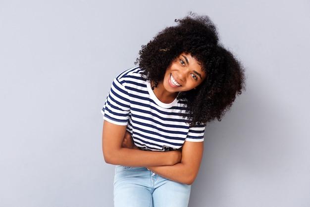 Souriante jeune femme afro-américaine sur fond gris avec les bras croisés