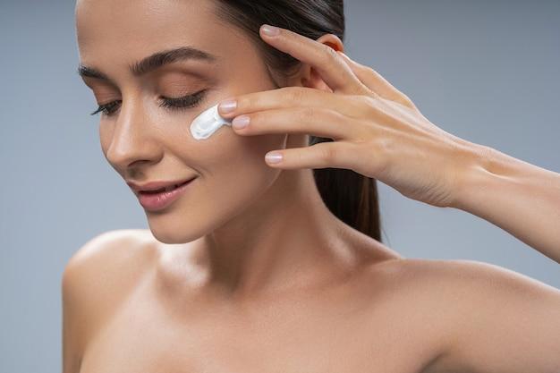 Souriante jeune femme à l'aide de crème pour le visage sur la joue