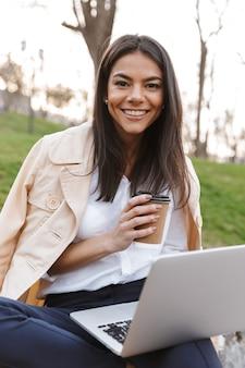 Souriante jeune femme à l'aide d'un ordinateur portable