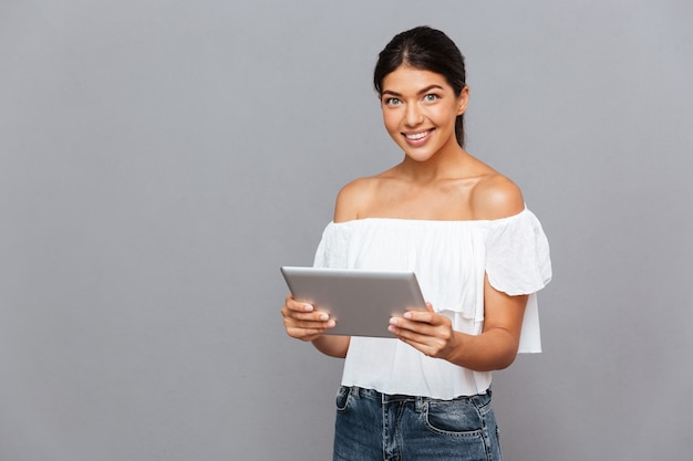 Souriante jeune femme à l'aide d'un ordinateur tablette et regardant l'avant isolé sur un mur gris
