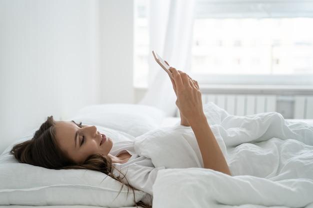 Souriante jeune femme à l'aide de téléphone intelligent mobile, couché et se détendre dans un lit confortable blanc à la maison