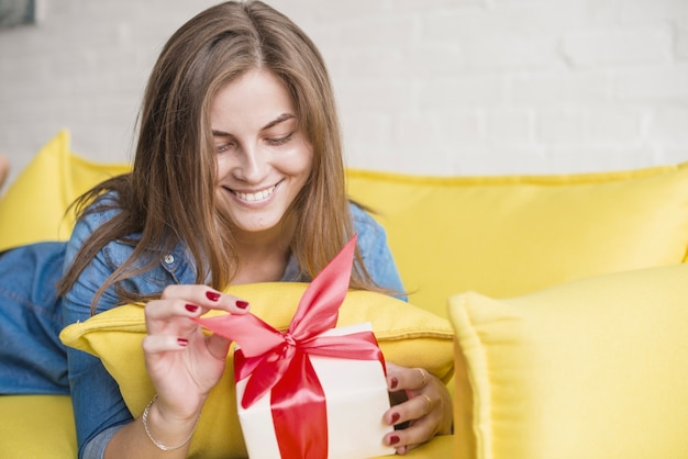 Souriante jeune femme allongée sur le canapé déballer son cadeau d'anniversaire