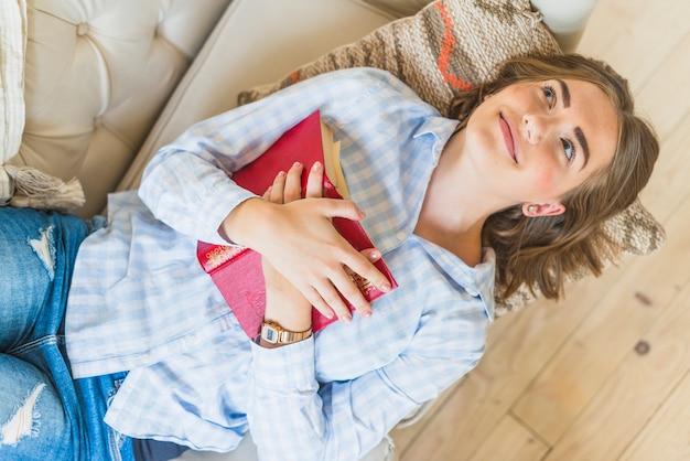 Souriante jeune femme allongée sur le canapé avec livre