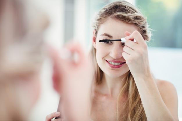 Souriante jeune femme appliquant du mascara