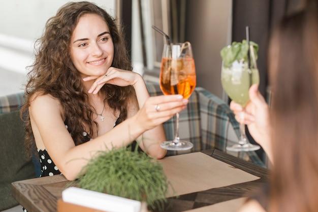 Souriante jeune femme appréciant boire avec son amie