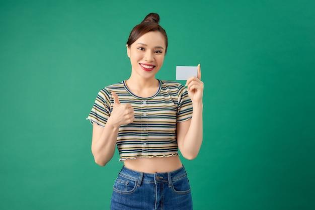 Souriante jeune femme asiatique debout sur le mur vert et tenant la carte de débit dans les mains.