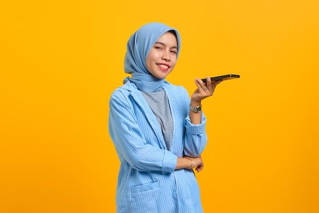 Souriante jeune femme asiatique parlant au téléphone portable et regardant la caméra sur fond jaune