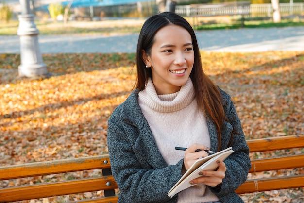 Souriante jeune femme asiatique portant un manteau assis sur un banc dans le parc, en prenant des notes dans un bloc-notes