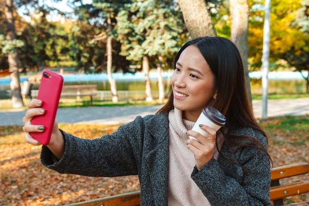 Souriante jeune femme asiatique portant un manteau assis sur un banc dans le parc, prenant un selfie, tenant une tasse de café