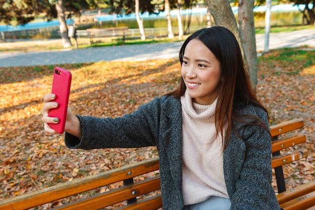 Souriante jeune femme asiatique portant un manteau assis sur un banc dans le parc, prenant un selfie