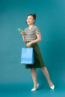 Souriante jeune femme asiatique avec des sacs de couleur shopping