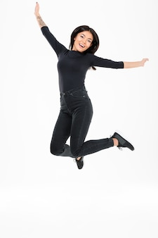Souriante jeune femme asiatique sautant