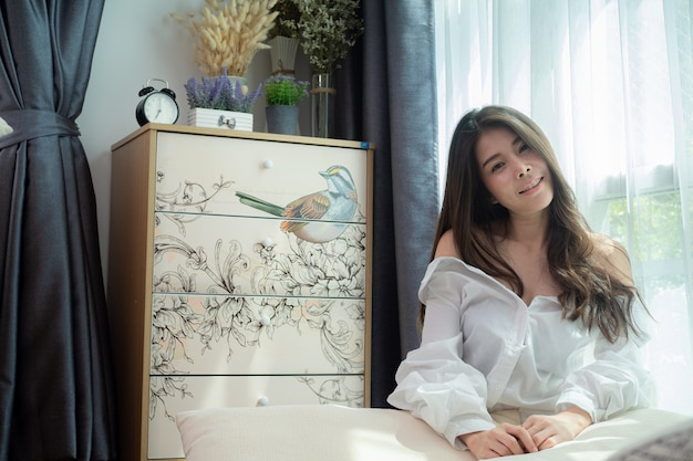 Souriante jeune femme asiatique se détendre dans le salon.