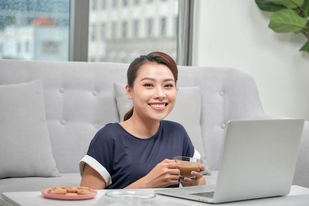 Souriante jeune femme asiatique tenant une tasse de café assise sur le sol avec un ordinateur portable et une carte de crédit à la maison