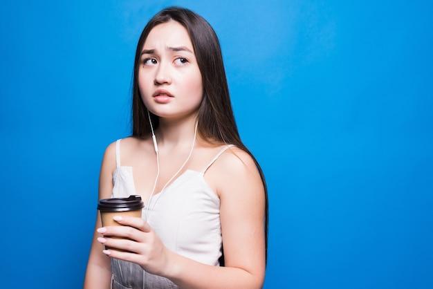 Souriante jeune femme asiatique tenant une tasse de café à emporter debout isolé sur un mur bleu