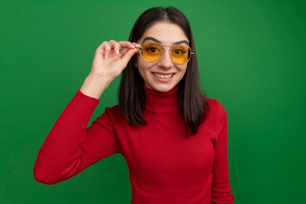 Souriante jeune femme assez caucasienne portant et attrapant des lunettes de soleil
