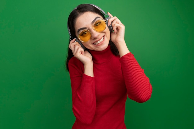 Souriante jeune femme assez caucasienne portant des lunettes de soleil et des écouteurs saisissant des écouteurs