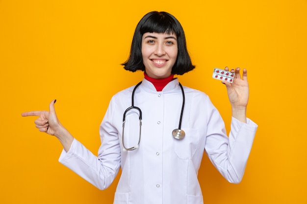 Souriante jeune femme assez caucasienne en uniforme de médecin avec stéthoscope tenant l'emballage de la pilule et pointant sur le côté