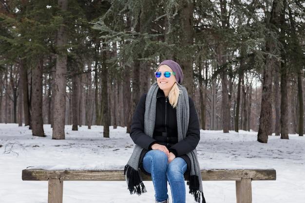 Souriante jeune femme assise sur un banc en bois en hiver dans la forêt enneigée
