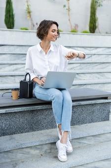 Souriante jeune femme assise sur un banc à l'extérieur