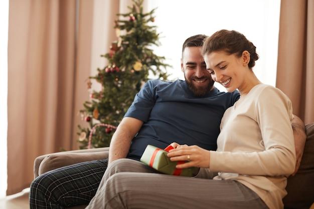 Souriante jeune femme assise sur un canapé dans le salon avec sapin de noël et déballant le cadeau de bo...