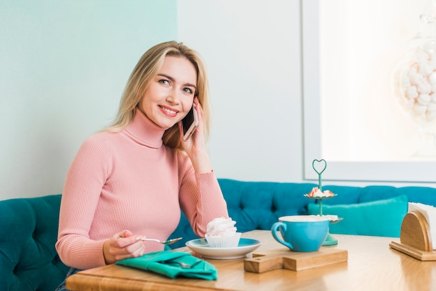 Souriante jeune femme assise dans un café, parler au téléphone mobile en appréciant cupcake et café