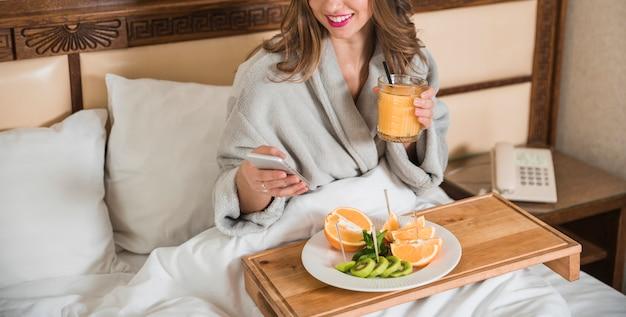 Souriante jeune femme assise sur un lit tenant un verre de message de jus de fruits sur téléphone mobile