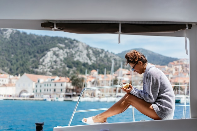 Souriante jeune femme assise sur le pont du yacht