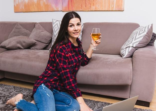Souriante jeune femme assise près du canapé tenant un verre en verre à vin