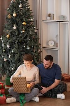 Souriante jeune femme assise sur le sol contre l'arbre de noël et ouverture d'une boîte-cadeau offerte par son petit ami
