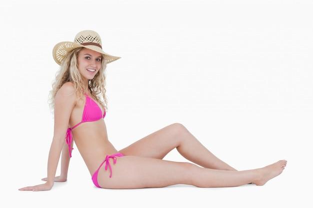 Souriante jeune femme assise sur le sol en maillots de bain